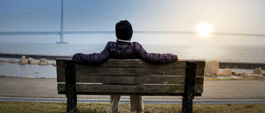 hombre que está sentado de espaldas y mirando al horizonte