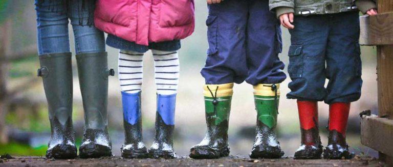 Imagen de la parte inferior (los pies con botas de barro) de 4 niños